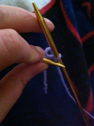 Transferir la nueva puntada de colar de la aguja derecha a la izquierda de la aguja mediante la inserción de la punta de la aguja izquierda en el bucle de la puntada que acaba de crear en la aguja derecha y deslizamiento