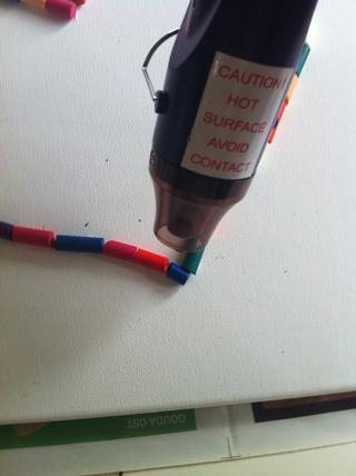 Ahora empieza a derretirse los crayones. Y asegúrese de girar el lienzo lo que los crayones fundición