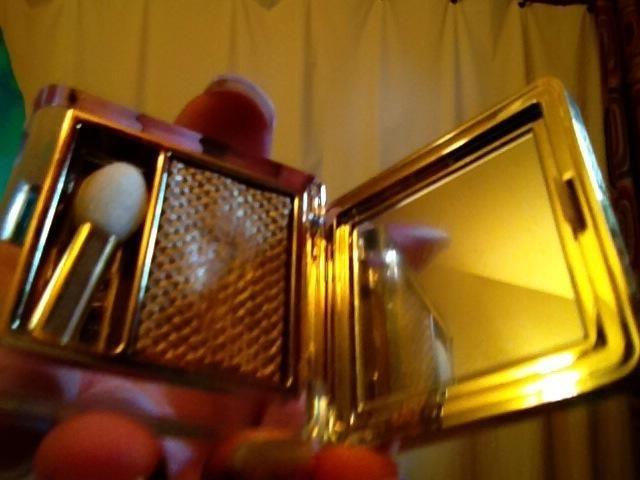 Saque su sombra de ojos de oro metálico y frotar el color desnudo fuera de su pequeño cepillo.