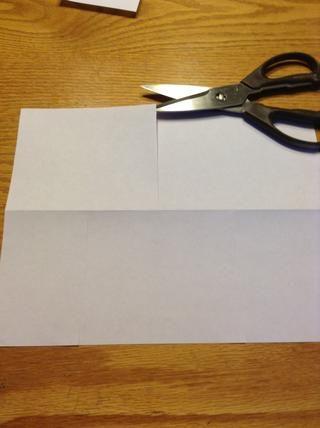 A continuación, hacer un corte en la mitad superior del papel que baja directamente en el centro de los dos cortes inferiores. Asegúrese de que la corte va todo el camino hasta el pliegue.