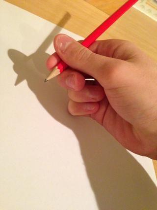 Empuje la articulación media de su dedo meñique en el papel, por lo que actúa como el punto de una brújula.