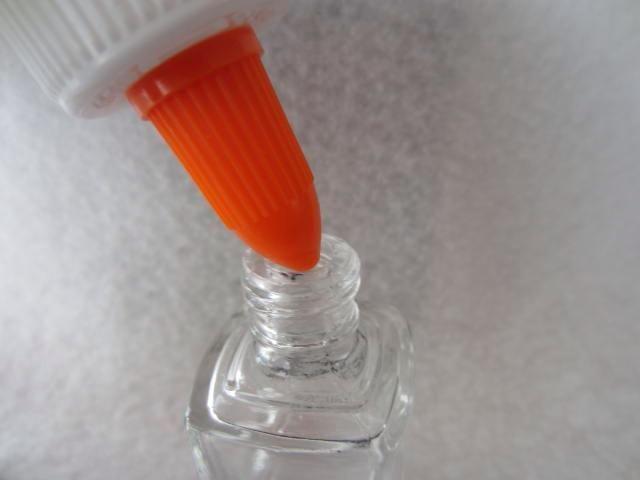 Squirt el pegamento en la botella de esmalte, dejando una pequeña cantidad de espacio en la parte superior.