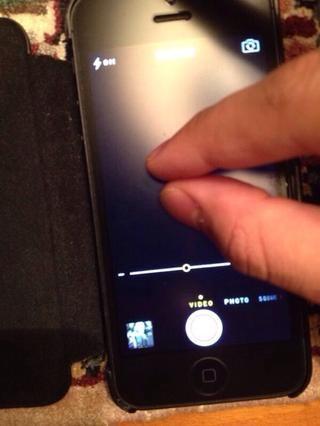Para acercar el modo de foto / vídeo, debes pellizcar la pantalla con dos dedos, y luego continuar pellizcar ya sea dentro o fuera para aumentar o disminuir el zoom. O utilice el control deslizante como en la imagen de arriba a +/-.
