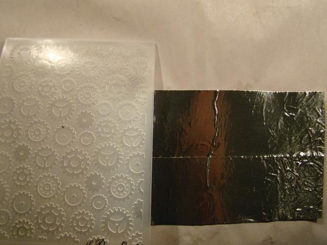 Uno de los compartimentos que quería tener un fondo falso metal. El uso de cinta de metal, me adherí a cartulina y el uso de un fundido textura, pasé por mi máquina de troquelado.