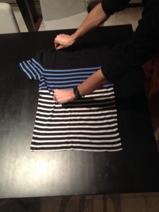 Coloque una mano alrededor de un tercio de la manera de la manga en la parte superior de la camiseta, y coloque la otra mitad de camino a mano por la camiseta pero en línea con la otra mano