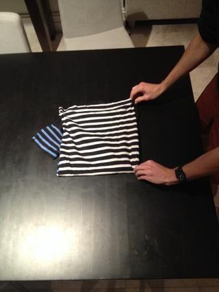 Coloque la camiseta sobre la mesa ...