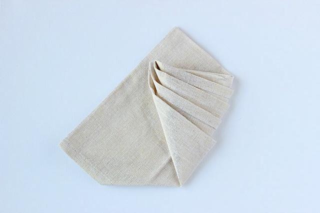 Gire la servilleta sobre, sosteniendo todas las capas que doblado en su lugar. A continuación, llevar la esquina derecha arriba y hacia la izquierda según lo representado.
