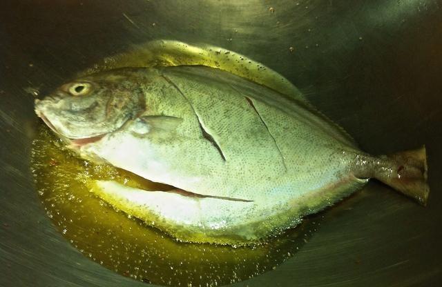 En mismo wok, usando el aceite infundido con ajo, profunda freír el pescado. Agregue más aceite si es necesario.