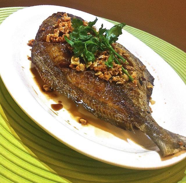 Traslado de pescado para un plato para servir. Top con ajo frito de oro y rociar con la salsa de soja oscura y la luz. Añadir 1 cucharada de aceite de ajo por encima. Adornar con perejil chino.