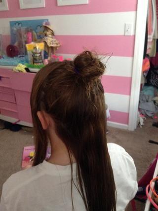 Tome un puñado de pelo en la parte superior de su cabeza y lo puso en un moño desordenado. Deja las hebras que se pone en la parte delantera donde están.
