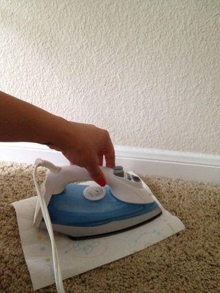 Coloque hierro en la parte superior de la cera durante unos pocos segundos. Don't press too hard on the iron. You won't burn the carpet or towel as long as you pay attention.