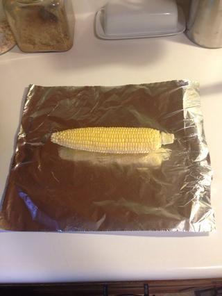 Saque un pedazo de papel de aluminio que está a unas pocas pulgadas más ancha que la de maíz.