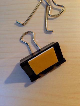 Tome un segundo clip de la carpeta, eliminar un mango y agregar un trozo de cinta de doble cara para ese lado.