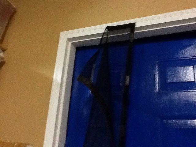 Alinear pestaña de velcro superior con el centro de la puerta. Retire la tapa blanca expuesta y adjuntar a puerta.