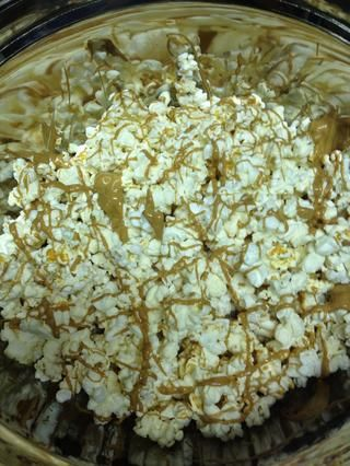 Rocíe la mantequilla de maní en las palomitas de maíz con una cuchara. Poner otra capa de palomitas en la llovizna y la mantequilla de maní. Repita hasta que todas las palomitas de maíz está cubierta.