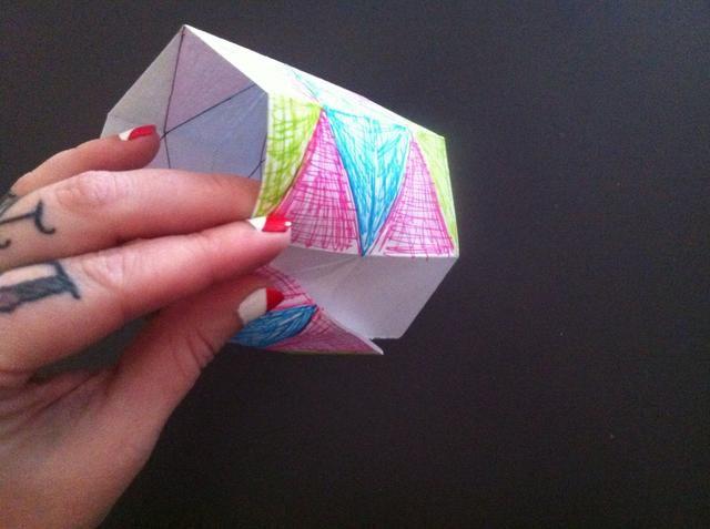 Formar un anillo y meter el borde no lo hiciste't color into the flaps of opposite edge like this.