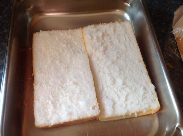 Cortar una torta de ángel por la mitad y colóquelo en un plato o bandeja.