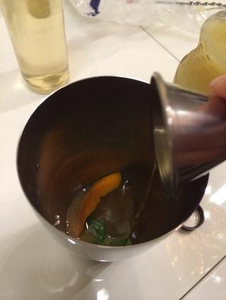 Agregue lo siguiente a una coctelera: 1 1/2 oz de brandy, 3/4 oz de jugo de limón, 1/2 oz jarabe simple, 1/2 oz de jarabe de jengibre, varios cubos de hielo, una tira de piel de naranja, y 3 hojas de menta .