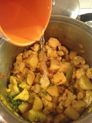 Añadir 100 ml de agua, revolver, tapar y dejar a fuego medio-alto durante 15 minutos o hasta que las papas estén suaves.