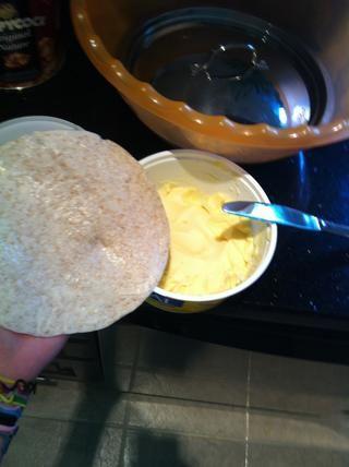 Aplicar mantequilla o margarina a un lado de la tortilla
