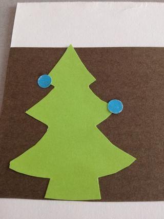 Tiempo para decorar el árbol! Perforación del papel de color para añadir adornos al árbol. Pegue abajo.