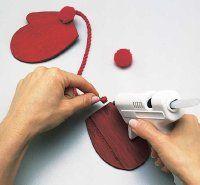 Pegue un cordón y un pom en el extremo del pulgar de cada una manopla.
