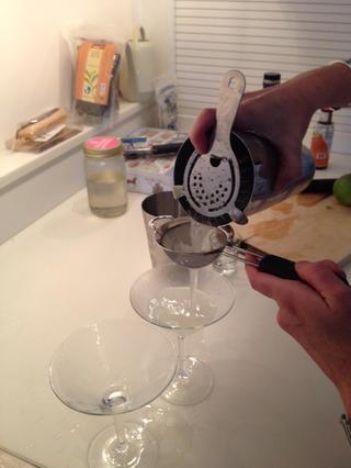 Mantenga el colador Hawthorne sobre el agitador y se vierte a través del colador de té para filtrar los trozos de hielo. Dividir la barrena entre los dos vasos.