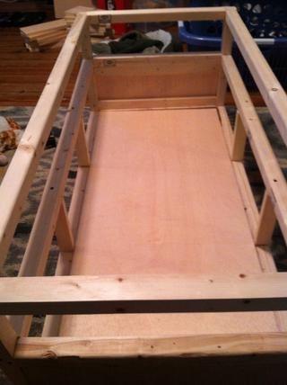Utilice su primera de tres hojas rasgadas de madera contrachapada para asegurar la base de la mesa