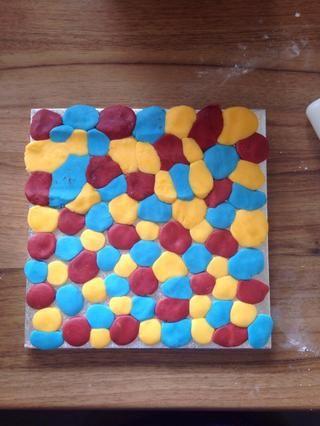 Cepille su tablero torta con agua y cubrirlo con pequeñas bolas de diferente color fondant, don't worry about the gaps