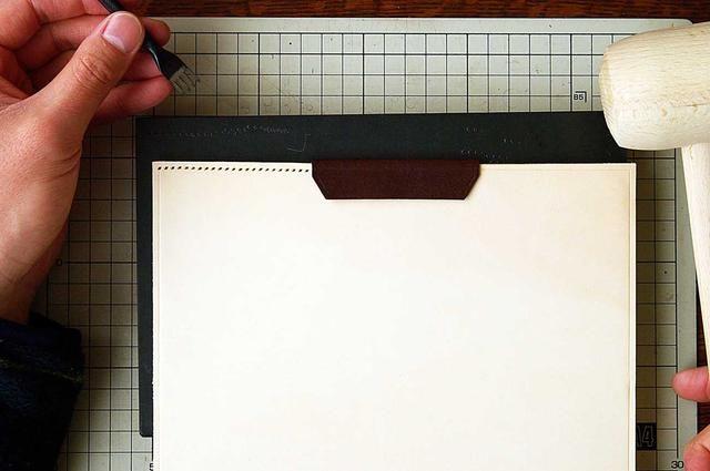 En este momento, trazar una línea en la cubierta portátil para hacer los line.Pierce coser con un martillo en la línea de costura.