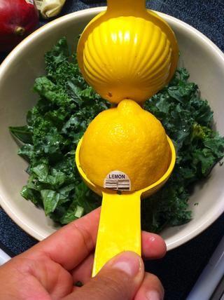 Coloca el col rizada en un bol grande y exprimir medio limón sobre la col rizada.
