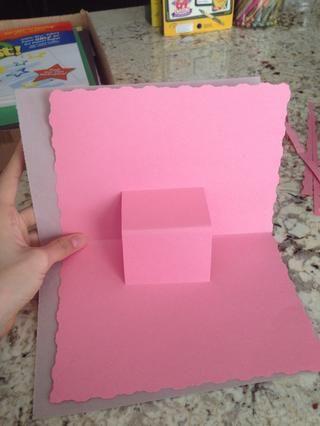 Ahora coloque el papel emergente en el interior de la otra hoja de papel. Este documento cubre el agujero emergente.