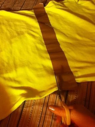 Y cortar justo debajo de la cinta hasta el final a través de la camisa!