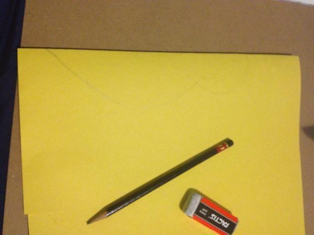 Tome su papel amarillo, doblar por la mitad y sacar esta forma en el borde doblado.