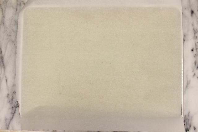 Coloque una hoja de papel de pergamino en la parte superior de la torta.