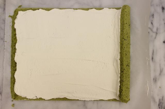Levante el papel de pergamino en el lado derecho de empezar a rodar la torta.