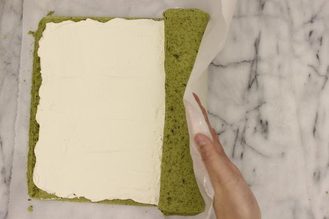Siga usando el papel de pergamino para ayudar a rodar la torta.