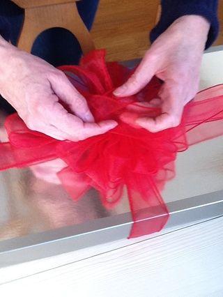 Coloque la cinta en la parte superior del paquete que ha cinta atada alrededor de ella