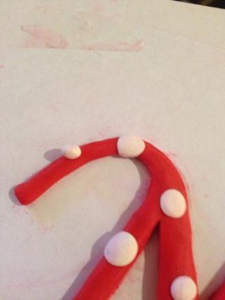 Añadí puntos poniendo primero bolas redondas de un segundo color de Sculpey alrededor de la parte superior de la carta. Luego aplanar la pelota para crear puntos.
