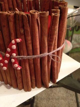 Después de que se seque el esmalte, coloque la letra con la cuerda que envuelve alrededor de los palos de canela. El hilo aquí se acaba envuelto alrededor de la pieza y escondido bajo.