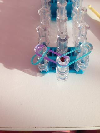Tome una banda de goma y el lugar en la clavija izquierda en la banda de goma púrpura.