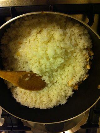 Una vez que el pollo es blanco añadir el arroz cocido.