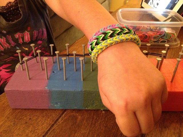 Aquí ella está mostrando algunas pulseras que ella hizo uso de su telar. Ella usó una aguja de crochet que ya teníamos en la mano para ayudar a aliviar las bandas más las clavijas o las uñas.