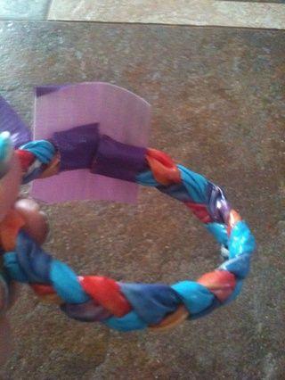 Cortar una tira un poco más largas que las que utilizó para atar los extremos fuera de su trenza. Hacer los extremos de su pulsera se unen y cinta adhesiva para que se mantengan juntos