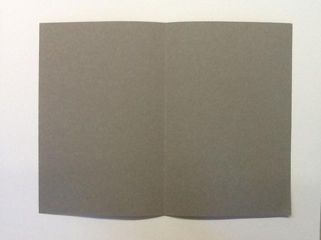 Luego, doblar el papel grueso en el medio en sentido longitudinal.