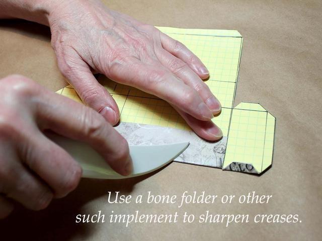 Utilice una carpeta de hueso o un elemento similar para afilar los pliegues.