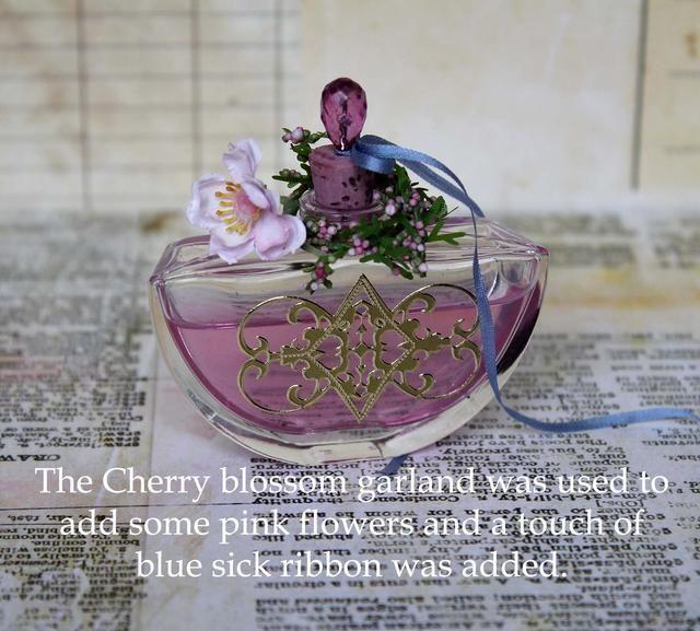 Para terminar la botella he añadido una cereza (flor) en la parte superior. Corte un pedazo de la guirnalda y se envuelve alrededor del cuello de la botella. Añadir una pequeña cinta azul para establecer si fuera poco.