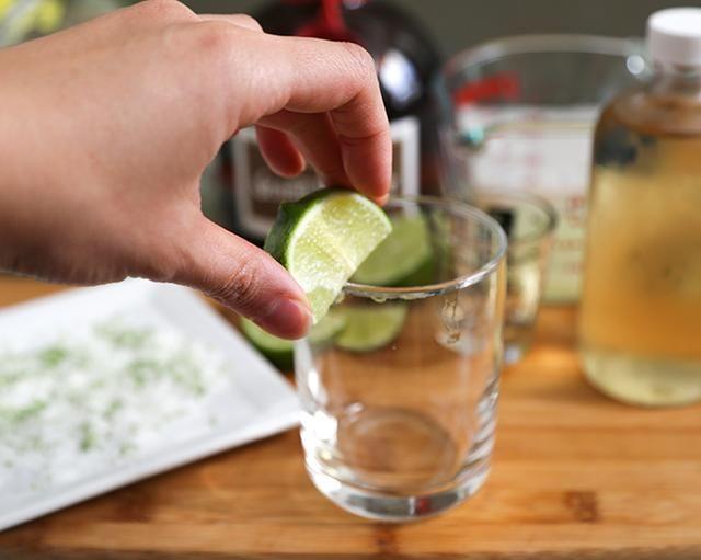 Humedezca el borde de servir de vidrio con rodaja de limón.