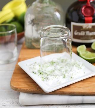 Invierta cristal en la mezcla de limón ralladura de sal. Cristal de la torcedura para asegurarse de que está revestida completamente.