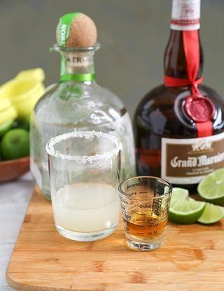 Gire el vidrio del lado derecho arriba. Vierta 1 1/2 oz tequila, seguido de 1 oz zumo de lima. Añadir 1/2 onza de licor de naranja.